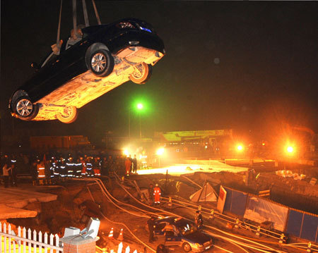 Rescuers work at the collapsed road where a subway tunnel was under construction in Hangzhou, capital of east China's Zhejiang Province, Nov. 15, 2008. At least one person is dead and 18 are missing and 13 vehicles were also trapped after the road caved in on a subway tunnel under construction in Hangzhou on November 15, 2008. [Xinhua photo]