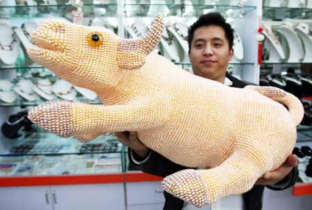 Photo taken on Nov. 17, 2008 shows a 85-cm-long, 55-cm-high ox figurine made of 130,000 pearls at a store of Suzhou, east China's Jiangsu Province.