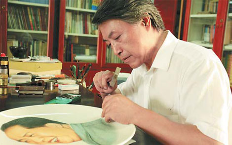 Li Ziyuan carves on a ceramic plate an image of late Chairman Mao Zedong at his studio in Zibo, Shandong province.