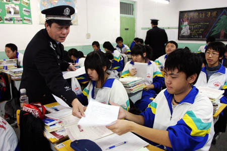 Policemen deliver the questionaire sheets on National Narcotics Ban Awareness for All the Public, to students in the classroom of Yuhong Middle School, in north China's Tianjin Municipality, Nov. 19, 2008. Policemen on duty get on the campus to promote the knowledges and discretion of students on their understanding of the drugs ban, discerning the narcotics ban, and self-protection from drugs as well. (Xinhua/Li Xiang)