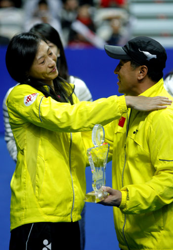 China's two-time Olympic champion Zhang Ning (L) embraces head coach Li Yongbo as she receives an award during a ceremony to mark her retirement with five other teammates from the national badminton team on the sidelines of the China Open badminton event in Shanghai, November 23, 2008. The 33-year-old veteran, who won gold in Athens and Beijing, has become the coach of the national women's team. [Xinhua]