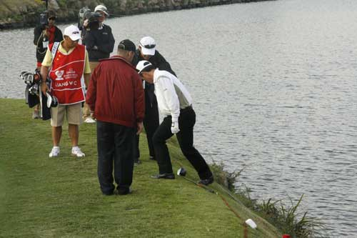 Debate about where Liang Wenchong plays his next shot. It was all in vain - he missed the chip and the putt. 