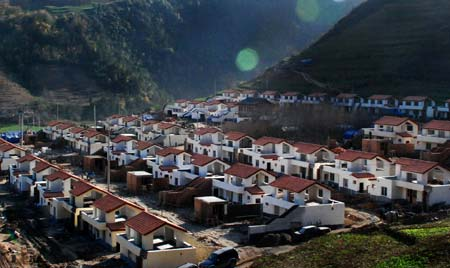 Photo dated on Dec. 8, 2008 shows the relocated Quanli village in Lueyang county, northwest China's Shaanxi Province. Two hundred and six quake-survived villagers have moved into their new houses in the newly-built village prior to the upcoming winter.(Xinhua Photo)