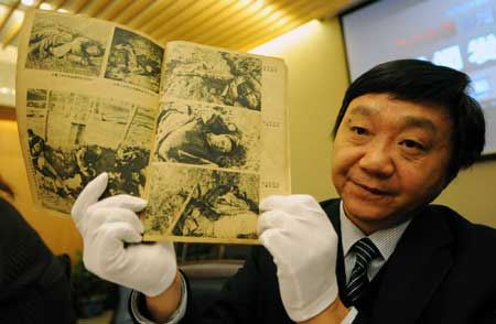 Zhu Chengshan, curator of the Memorial Hall of the Victims of the Nanjing Massacre shows a piece of evidence from the Nanjing Massacre and other Japanese atrocities during WWII, in Nanjing, east China's Jiangsu Province, on Dec. 11, 2008. The 816 pieces of new evidence, including documents, videos, books, calligraphy and paintings, were collected this year mainly from China, the United States and Japan. [Xinhua]