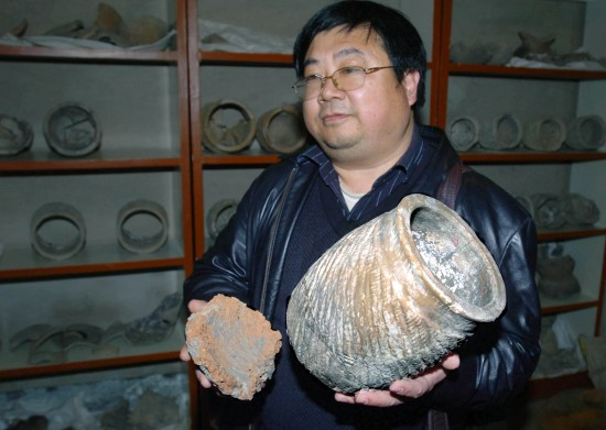 Wang Shougong, archaeologist and deputy director of the Institute of Cultural Relics and Archaeology of Shandong Province, displays a restored galeiform vessel. The vessel is 30 centimeters in height and 20 centimeters in diameter. [Wu Zengxiang/Xinhua]