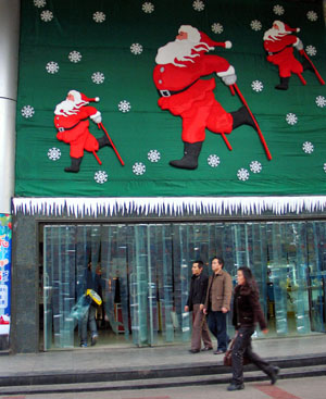 A Santa Claus decoration is seen on the gate of a shopping mall in Guiyang, capital of southwest China's Guizhou Province, Dec. 16, 2008.