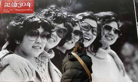 A girl appreciates an old photo taken in 1980 at an exhibition featuring China's 30 years' reform and opening-up at Wangfujing Street in Beijing, China, on Dec. 16, 2008.