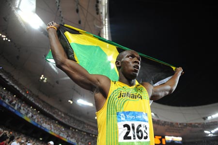 Jamaica's Usain Bolt displays the national flag of Jamaica after taking men's 100m final at the National Stadium, also known as the Bird's Nest, during Beijing 2008 Olympic Games in Beijing, China, Aug. 16, 2008. Usain Bolt claimed the title of the event and broke the world record.