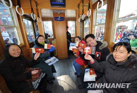 Visitors pose with tickets on a tram beginning trial operation in Qianmen Street, Beijing, Jan. 1, 2009.(Xinhua Photo)