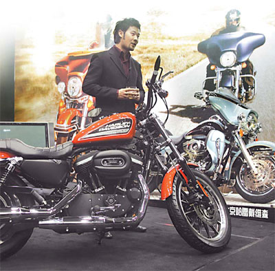A man stands beside a Harley Davidson motocycle at the Top Essence Luxury Show in Beijing in late November. Over a third of the items in the show were reportedly displayed for the first time in Asia. [China Daily]