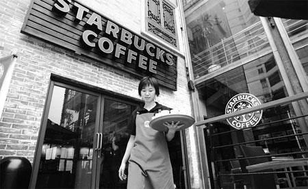 A Starbucks employee serves at a shop in Chongqing, southwestern China. [China Daily]