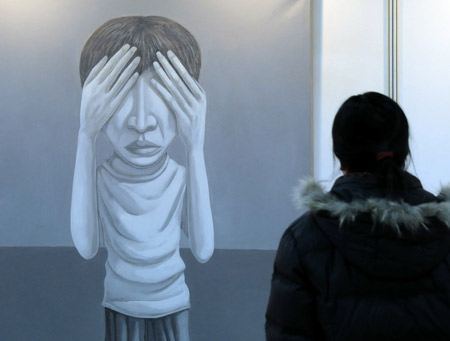 A woman views a painting during the first art exhibition of China, South Korea, Japan and Russia, in Harbin, capital of northeast China's Heilongjiang Province, Jan. 5, 2009. Fourteen artists from the four countries presented their creations during the 10-day art show, opened on Monday. [Xinhua]