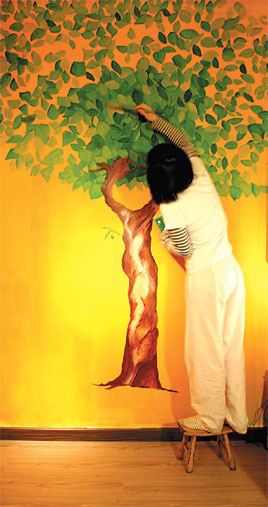 A tree grows under the brush of art designer Chen Lijuan. The painting adds a lively touch to her apartment in Beijing.