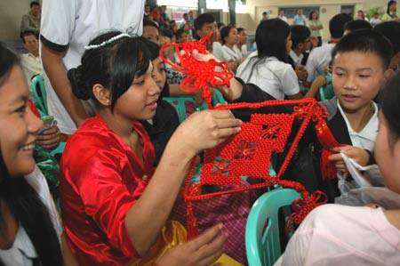 Philippine students receive a Chinese knot as a gift from their Chinese companions at the Raja Suliman Science And Technology High School in Manila, the Philippines, Jan. 15, 2009. Invited by Philippine President Gloria Macapagal-Arroyo, a group of 100 children who survived a devastating earthquake in China last May arrived in the Philippines on Sunday for a week-long trip. [Xu Lingui/Xinhua]