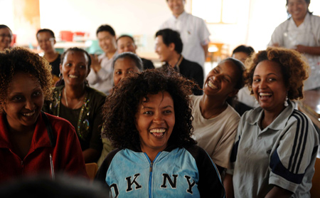 Ethiopian workers of China's ZTE Corporation watch TV as they celebrate the Chinese Lunar New Year with Chinese workers in Addis Ababa, capital of Ethiopia, Jan. 25, 2009.