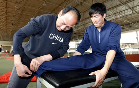 Sun Haiping (L), the coach of Chinese 110m hurdle star Liu Xiang works on Liu's foot prior to a training session in Shanghai, east China, March 10, 2009. [Xinhua]
