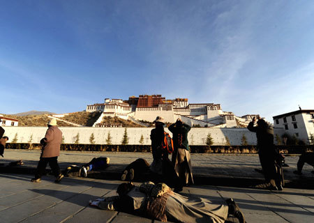 Tibetan pilgrims turn the pray wheels in front of the Potala Palace during the Grand Summons Ceremony in Lhasa, southwest China's Tibet Autonomous Region, on March 10, 2009. [Xinhua photo]