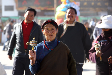 An elderly Tibetan holding a prayer wheel walks on the famous market street, Pogor near the Jokhang Temple in central Lhasa, capital of southwest China's Tibet Autonomous Region, March 10, 2009. (Xinhua photo]