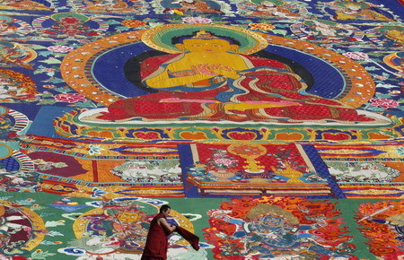 An ethnic Tibetan monk walks in front of a giant 'thangka', a sacred painting on cloth, to be displayed on a hill outside a monastery in Tongren, northwest China's Qinghai province Monday, Feb. 2, 2009. [Photo: China Daily]