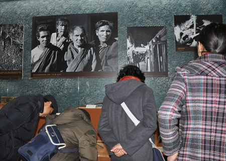 Visitors look at objects that were used by serf owners to torture serfs in old Tibet at an exhibition marking the 50th anniversary of the Democratic Reform in Tibet Autonomous Region in Beijing, Feb. 25, 2009. (Xinhuanet Photo)