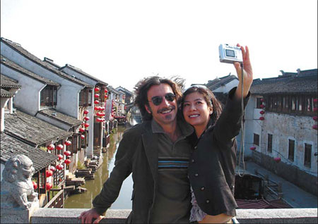 Tourists pose for a photo on the famous Shantang ancient bridge in the scenic city of Suzhou, Jiangsu province, on Nov 24, 2007, while enjoying the bright sunshine during the winter months.