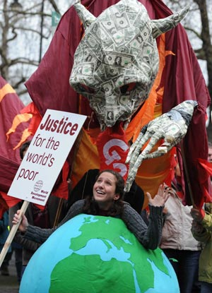A girl carrying a model of the earth gestures during a demonstration in London on March 28, 2009. The Put People First group, an alliance of more than 150 unions, on Saturday organized the demonstration, calling on the leaders of the Group of 20 Countries (G20) to adopt sustainable policies that can lead the world out of recession. The demonstrators also urged the leaders to attach importance to global environment protection and to stablize the world political situation. The G20 leaders will meet in London on April 2. (Xinhua/Zeng Yi)
