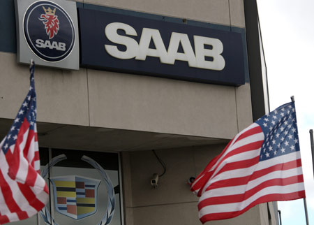 National flags of the United States flutter in front of the logo of Saab at a car dealership in New York, the United States, April 7, 2009. Saab Automobile, the troubled Swedish unit of Genral Motors Corp, has been contacted by 20 potetial buyers, with a sale planned in June, the carmaker