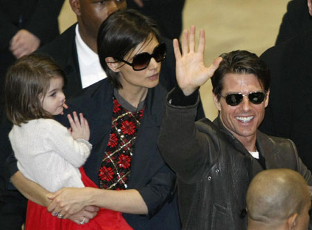 Actor Tom Cruise (R) waves to fans upon his arrival with his wife Katie Holmes (C) and their daughter Suri at Narita International Airport March 8, 2009. Tom and his family flew into Japan on Sunday to promote his movie 'Valkyrie'.