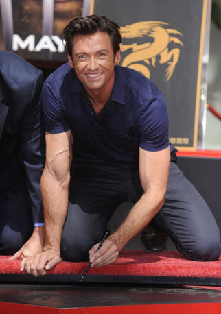 Hugh Jackman signs his name during a ceremony where the actor places his hand and foot prints in cement in front of the Grauman's Chinese Theatre in Hollywood April 21, 2009.