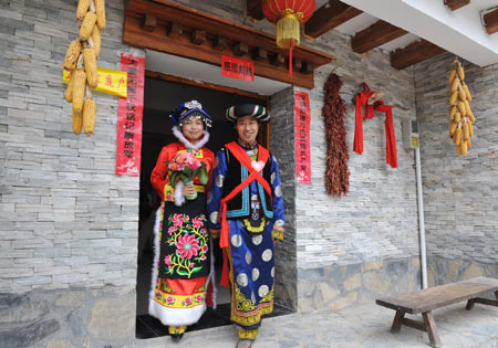 Bridegroom Tang Zhiguo (R) and his bride walk to attend wedding at the Jina Qiang Ethnic Minority Village of Beichuan County, southwest China's Sichuan Province, April 26, 2009. Twenty new couples held group wedding here on Sunday. [He Junchang/Xinhua] 