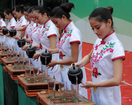 Girls perform the tea-serving proceeding at the opening ceremony of the Enjoying Fragrant Tea with Health in Guiyang, southwest China's Guizhou Province, May 26, 2009. The 5-day activity will feature art performance related to tea culture.