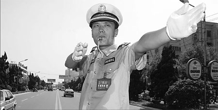 A policeman directs the traffic with his shirt soaked in sweat. [Bai Xianglin/China Daily]