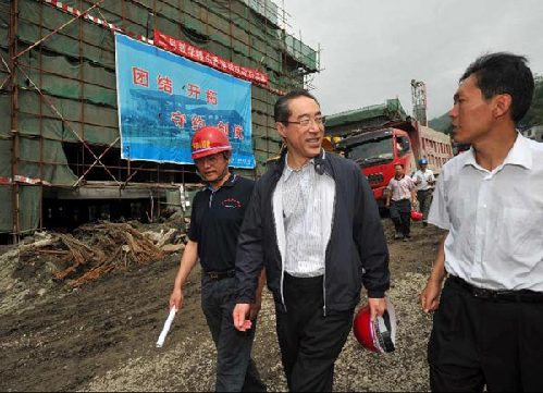 Hong Kong Chief Secretary Henry Tang, left, is briefed on the re-construction progress of the Shuimo Secondary School in Wenchuan, in Sichuan Province on July 5th, 2009. [Photo courtesy of the Hong Kong SAR Government]