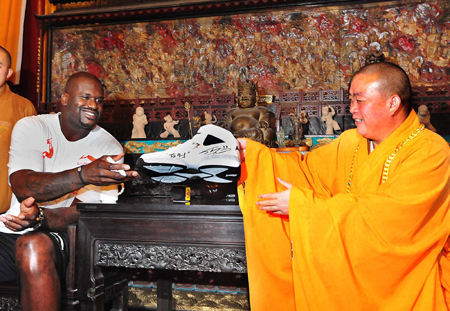 NBA Cleveland Cavaliers center Shaquille O'Neal (L) presents a basketball shoe with his signature to Shi Yongxin, abbot of Shaolin Temple, during his promotional tour in Shaolin Temple, central China's Henan province, July 13, 2009. (Xinhua photo)