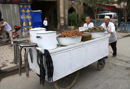 A vendor pulls a food cart in Kashgar city, northwest China's Xinjiang Uygur Autonomous Region, July 12, 2009. Businesses have recovered and prices have fallen to normal level in the city.