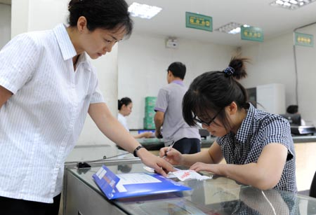 Student of Xinjiang University Tang Juan (R) fills in a form with the help of an employee at the Santunbei Branch of the Urumqi Post Bureau in Urumqi, capital of northwest China's Xinjiang Uygur Autonomous Region, on July 14, 2009. By now, all the 33 delivering outlets, 69 community outlets and 107 business outlets of the Urumqi Post Bureau have returned to normal work after the deadly riot on July 5. (Xinhua/Xu Liang)