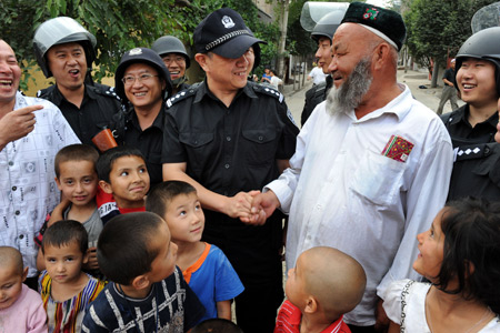 Xu Tao (C), a member of the special police force, shakes hands with an elder Uygur man, on Pingding Hill in Urumqi, capital of northwest China's Xinjiang Uygur Autonomous Region, July 14, 2009.