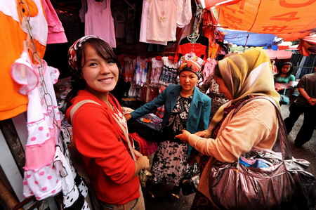 Shoppers buy clothes at a Bazaar on Han Ren Jie in Yining, in northwest China's Xinjiang Uygur autonomous region, July 19, 2009. Han Ren Jie, which literally translates to Han people street, was built in the Qing Dynasty (1644-1911AD), and remains a major commercial area in Yining today. [Xinhua]