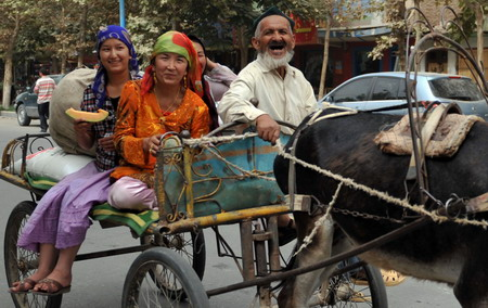 A family riding on a donkey cart returns from a bazaar in Hotan, northwest China's Xinjiang Uygur autonomous region, July 19, 2009. [Xinhua]