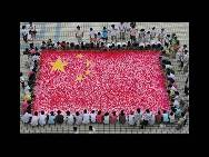 Students paint a national flag of 60 square meters with their hands ahead of the 60th anniversary of the founding of the PRC on July 21 in Hanshan County of Anhui Province. Many festivities are being planned for this year's National Day.(China.org.cn / CFP)