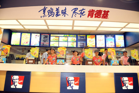 Staff members of a KFC store in the international bazar wait for customers in Urumqi, capital of northwest China's Xinjiang Uygur Autonomous Region, July 23, 2009. The KFC store in the international bazar, which was closed after the July 5 riot, was reopened on Thursday. (Xinhua/Sadat)
