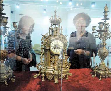 Visitors admire a 19th-century copper table clock and candle stick. [Shanghai Daily]