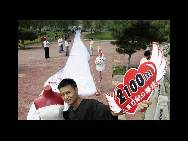 Zhao Peng, 28, holds a sign to celebrate as the world's longest wedding dress train he makes to please his bride-to-be is unveiled at Jiangbin Park on August 1 in Jilin city of Jilin Province. It takes nearly three hours to unveil the train, which is 2,162 meters long and 1.5 meters wide. The train is set to break the existing world record of the longest wedding dress train, which measures 1579 meters. (China.org.cn / CFP)