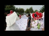A view of the world's longest wedding dress train made by Zhao Peng to please his bride-to-be on August 1 in Jilin city of Jilin Province. It takes nearly three hours to unveil the train, which is 2,162 meters long and 1.5 meters wide. The train is set to break the existing world record of the longest wedding dress train, which measures 1579 meters. (China.org.cn / CFP)