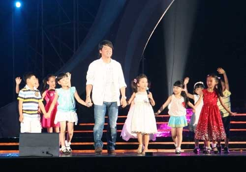 Popular star Emil Chau performs with children. [By Ni Yuanjin/China.org.cn]