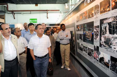 Diplomats watch an exhibition on the July 5 riot in Urumqi, capital of northwest China's Xinjiang Uygur Autonomous Region, Aug. 11, 2009. Diplomats from 26 countries and regions to China began a five-day visit to Xinjiang on Monday, a month after the deadly riot in the regional capital of Urumqi which left 197 people dead and more than 1,600 others injured. (Xinhua/Sadat)