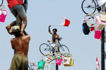 A contestant gets a prize hung at the top of a greasy pole during the celebrations of Indonesia's Independence Day in Jakarta Aug. 17, 2009. Indonesia on Monday celebrated its 64th anniversary of independence. (Xinhua/Yue Yuewei)