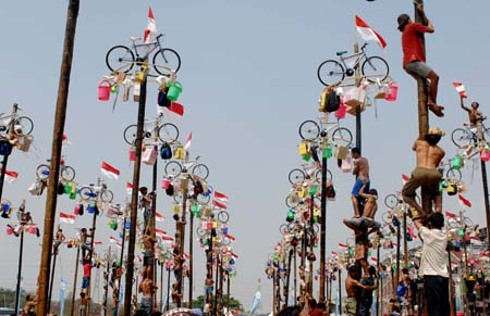 Contestants help one another to climb greasy poles to reach prizes hung at the top during the celebrations of Indonesia's Independence Day in Jakarta Aug. 17, 2009. Indonesia on Monday celebrated its 64th anniversary of independence. (Xinhua/Yue Yuewei)