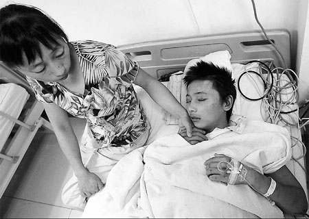Pu Liang's mother cares for him at the hospital after he was severely beaten at an Internet rehab center. Pu was rescued by police.
