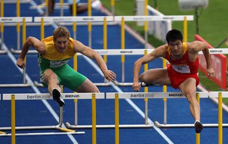 Shi Dongpeng (R) of China competes in the first round of Men's 110M Hurdles in the 12th IAAF World Championships in Athletics in Berlin, Germany, Aug. 19, 2009. Shi Dongpeng was qualified to the next round with 13.56 seconds.